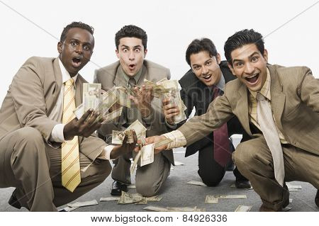 Portrait of four businessmen crouching and holding currency notes