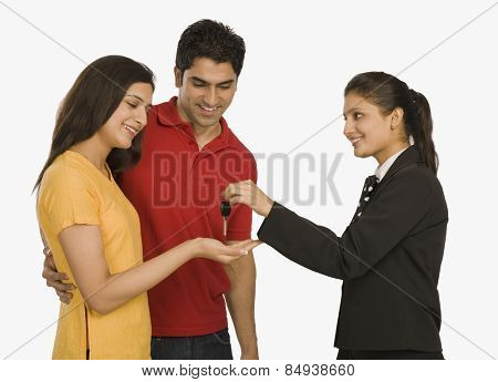 Businesswomen giving a car key to a woman