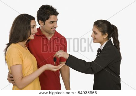 Businesswoman giving a car key to a woman