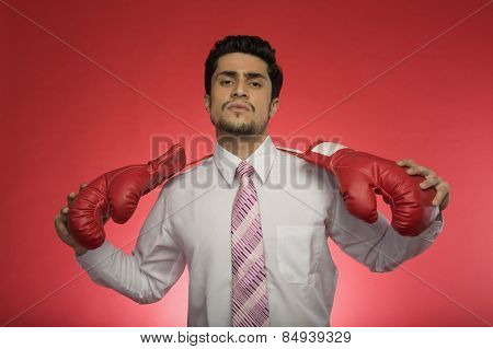 Portrait of a businessman holding boxing gloves