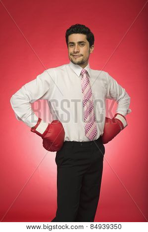 Portrait of a businessman wearing boxing gloves and standing with arms akimbo