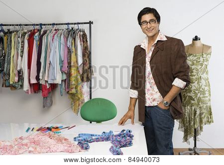 Portrait of a tailor standing in a clothing store and smiling