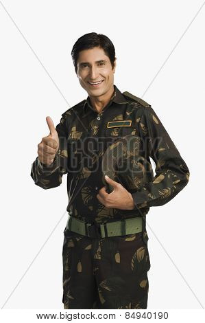 Portrait of an army soldier showing thumbs up and smiling