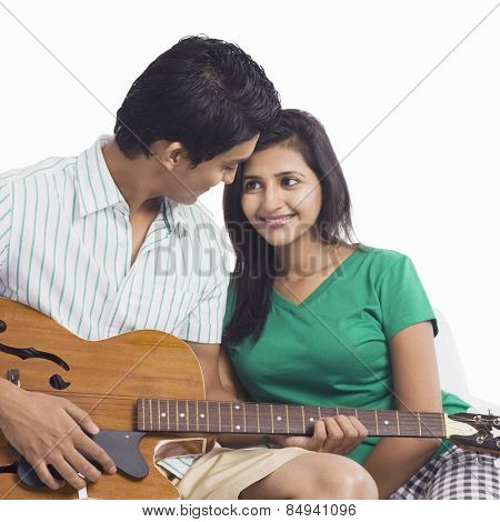 Man playing a guitar beside a woman