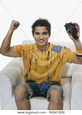 Portrait of a man cheering while playing video game