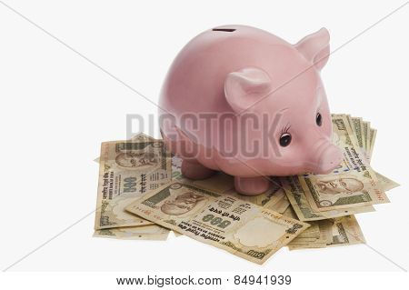 Piggy bank on Indian currency notes