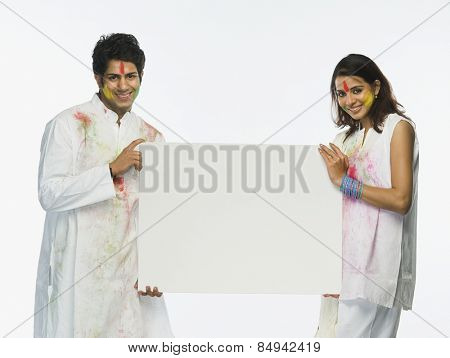 Couple holding a placard on Holi