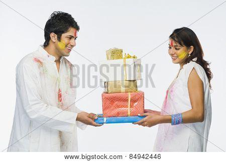 Couple holding Holi gifts