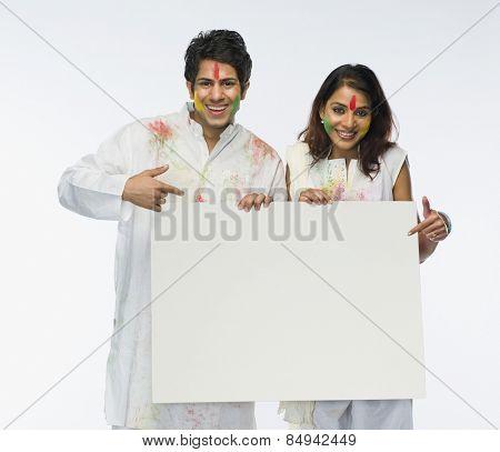 Couple holding a placard on Holi