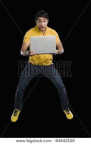 Man working on a laptop and looking surprised
