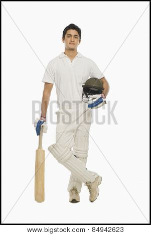Portrait of a cricket batsman standing with a bat and a helmet