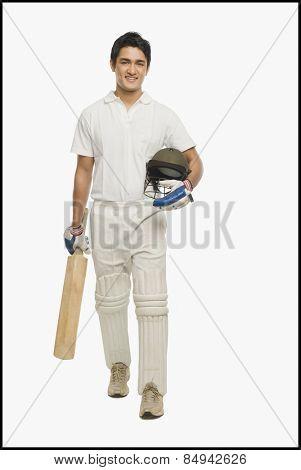 Portrait of a cricket batsman walking with a bat and a helmet