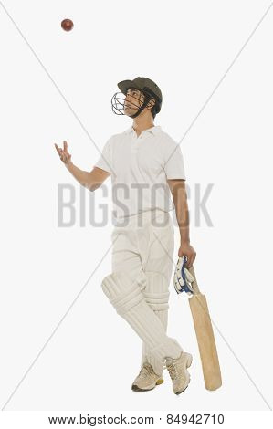 Cricket batsman tossing a cricket ball