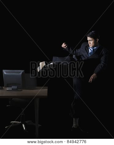 Frustrated businessman kicking a desktop pc