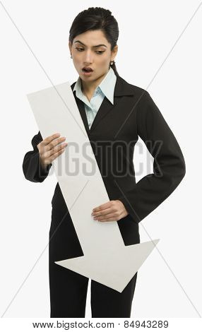 Businesswoman holding a downward arrow sign