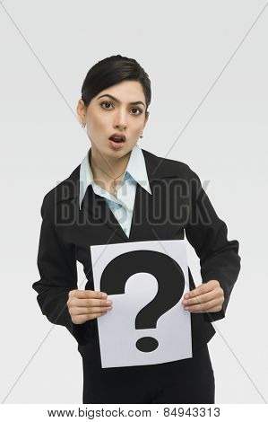Businesswoman holding a card with question mark