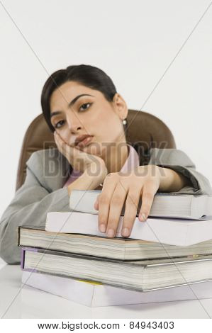 Businesswoman with stack of books on a desk