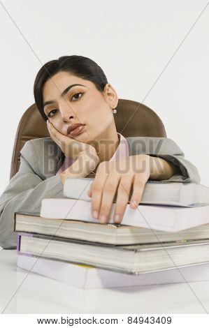 Businesswoman with a stack of books on a desk