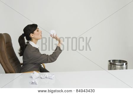 Businesswoman throwing crumpled paper into a wastepaper basket