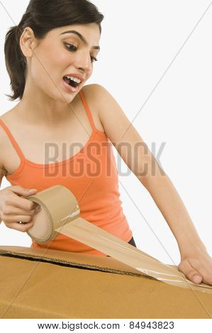 Woman packing cardboard by packing tape