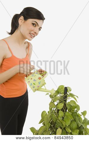Woman watering plant with a watering can