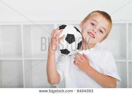 cute young boy holding soccer ball
