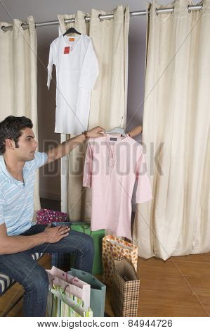 Man giving a kurta to a woman to try on in a store