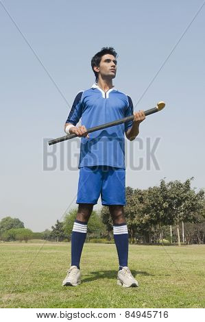 Man holding a hockey stick in a field