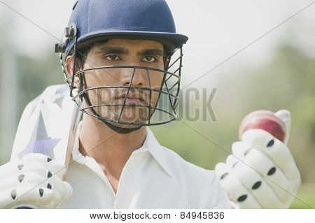 Cricket batsman holding a cricket bat with a cricket ball