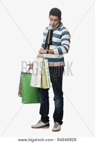 Man checking the time and carrying shopping bags