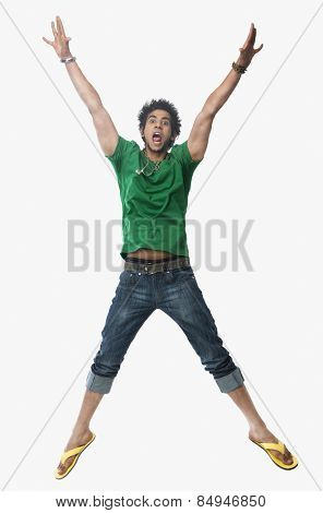 University student jumping with arms raised