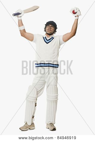 Cricket batsman holding a ball and bat with his arms raised