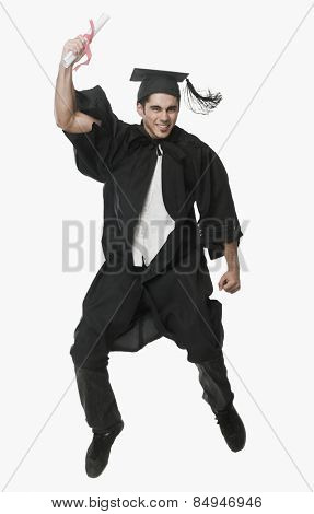 Man in a graduation gown holding a diploma and jumping