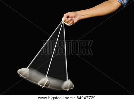 Close-up of a person's hand swinging a stone pendulum