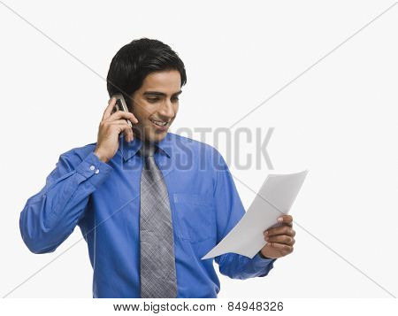 Businessman talking on a mobile phone while reading a document