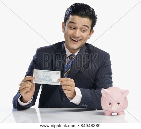 Businessman holding currency note and looking at piggy bank