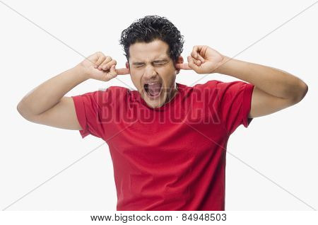 Man screaming holding his ears