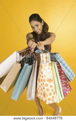 Woman showing shopping bags and smiling