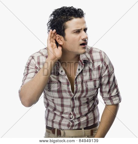 Man trying to listen with a cupped hand on his ear