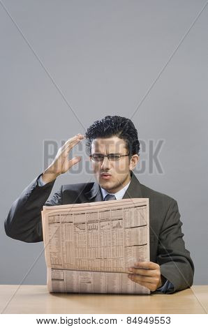 Businessman reading a financial newspaper and looking disappointed
