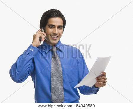 Businessman talking on a mobile phone and holding a document