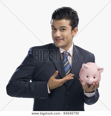 Businessman holding piggy bank