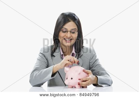 Businesswoman inserting a coin into piggy bank