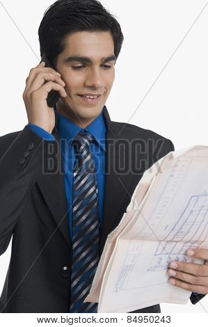 Real estate agent holding blueprint and talking on mobile phone