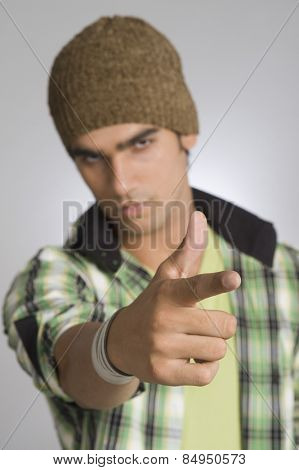 Portrait of man showing gun sign