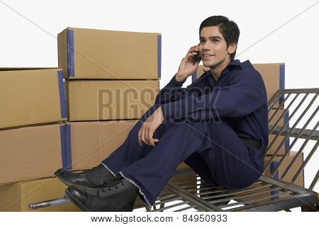 Store incharge sitting on a hand truck and talking on a mobile phone