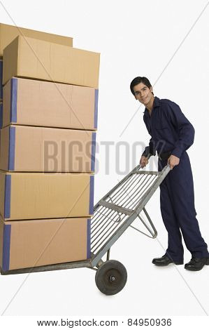 Storekeeper carrying cardboard boxes on a hand truck