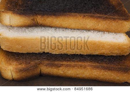 Slice of bread between two burnt toasts