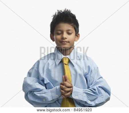 Boy dressed as a businessman and praying