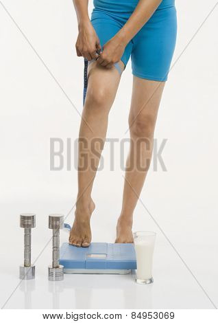 Woman standing on a weight scale and measuring her thigh